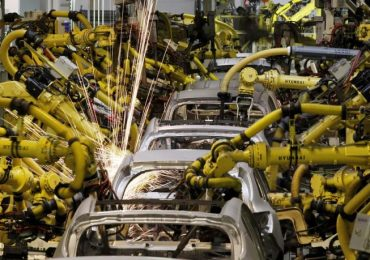Multiple Robots are busy assembling Parts, grinding and wielding at the Volkswagen Factory in Germany.